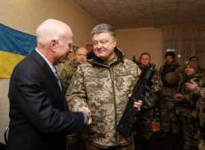 """A handout photo released by the Ukrainian Presidential press service shows Ukrainian President Petro Poroshenko (R) presenting the Ukrainian award weapon to the Chairman of Senate Armed Services Committee, US Senator John McCain (L) during their working trip to the Donetsk region to congratulate the Ukrainian marines on the upcoming New Year in Shyrokine village on December 31, 2016. The President together with the delegation of the US Senators visited the frontline positions of the Ukrainian Naval Forces of Ukraine, which holds the defense line in Shyrokyne. / AFP PHOTO / UKRAINIAN PRESIDENTIAL PRESS SERVICE / MIKHAIL PALINCHAK / RESTRICTED TO EDITORIAL USE - MANDATORY CREDIT """"AFP PHOTO / UKRAINIAN PRESIDENTIAL PRESS SERVICE / MIKHAIL PALINCHAK"""" - NO MARKETING NO ADVERTISING CAMPAIGNS - DISTRIBUTED AS A SERVICE TO CLIENTS"""